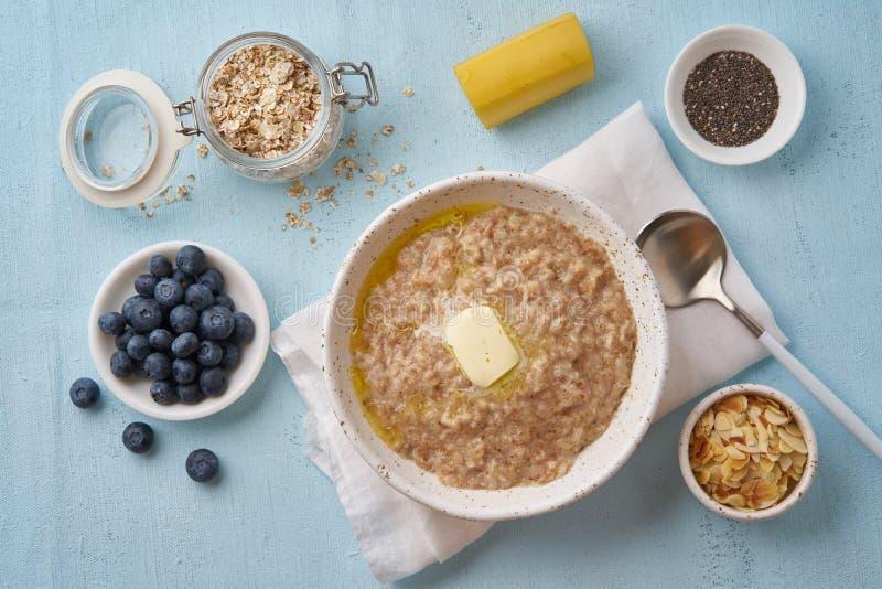 Hafermehl mit Butter und Bel?gen Blaubeeren, Chia-Samen, Mandelflocken, Banane Beschneidungspfad eingeschlossen lizenzfreie stockbilder
