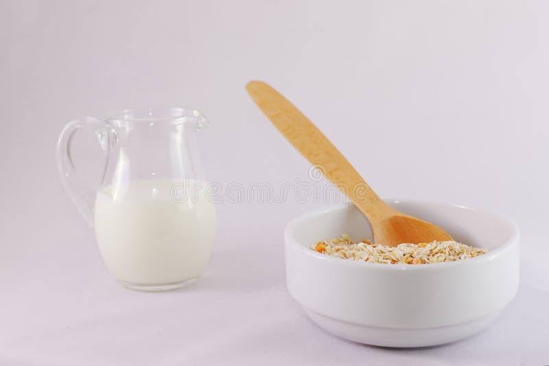 Hafermehl mit gelben Aprikosenstücken in einer tiefen weißen Schüssel, ein hölzerner Löffel, ein Glas Milch stockfotografie