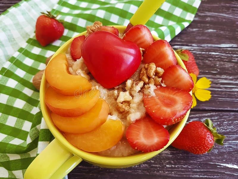 Hafermehlbrei, Aprikose, Erdbeere, Herz auf einem hölzernen Hintergrund lizenzfreies stockfoto