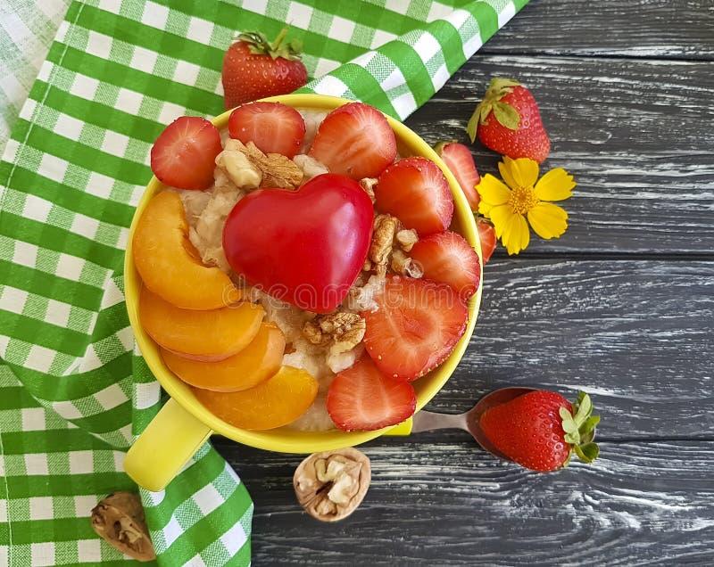 Hafermehlbrei, Aprikose, Erdbeere, Nahrungsfrühstücksherz auf einem hölzernen Hintergrund stockfoto