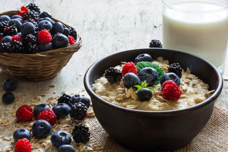 Hafermehlbrei in der rustikalen Schüssel mit frischen reifen Beeren und Glas Milch Gesundes Frühstück lizenzfreie stockfotos