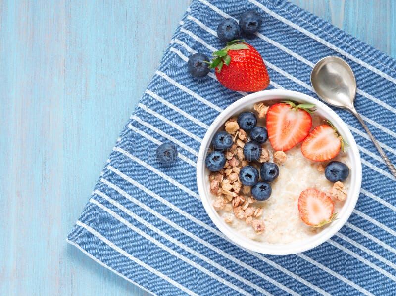 Hafermehlbrei mit frischer Erdbeere, Blaubeere, Granola auf Kontrastblauhintergrund Healty Frühstücks-Draufsicht lizenzfreie stockbilder