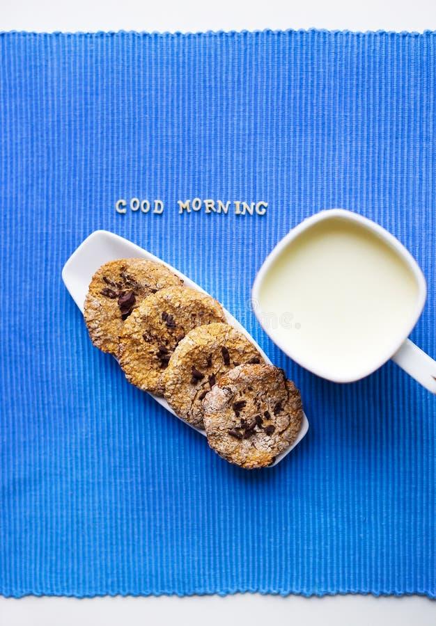 Hafermehlplätzchen in einer weißen Platte mit einer Schale Milch, die guten Morgen sagt lizenzfreie stockfotografie