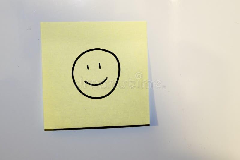 Haftnotiz mit einem glücklichen Gesicht gezeichnet stockbild