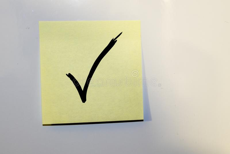 Haftnotiz mit einem Prüfzeichen lizenzfreie stockfotografie