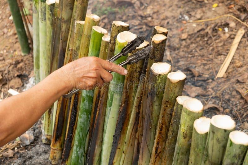 Haga el arroz pegajoso con la leche de coco asada en un cilindro de bambú de las juntas de la longitud, fuga de Khao es postre du fotos de archivo
