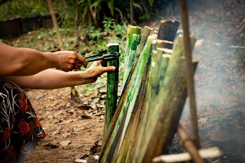 Haga el arroz pegajoso con la leche de coco asada en un cilindro de bambú de las juntas de la longitud, fuga de Khao es postre du imagenes de archivo