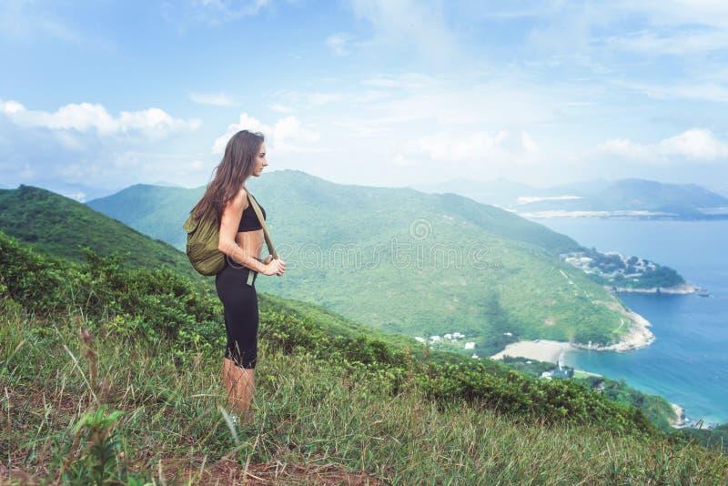 Haga excursionismo al viajero femenino que se coloca en la colina que mira el mar y las montañas Arrastre el corredor que toma un imagen de archivo libre de regalías