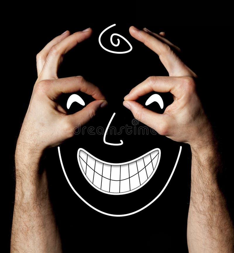Haga frente con la expresión facial de la felicidad de las manos en fondo negro imágenes de archivo libres de regalías