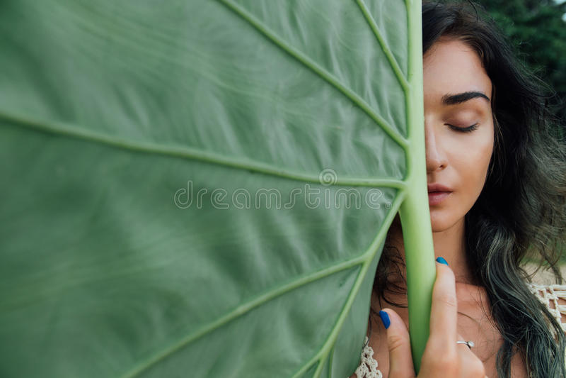 Haga frente a la mujer joven atractiva contra un árbol tropical de la hoja verde grande foto de archivo libre de regalías