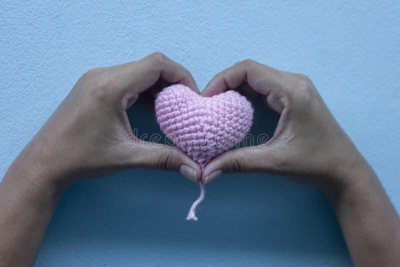 Haga a ganchillo el corazón con la forma del corazón del hilado y de la mano para el día de tarjeta del día de San Valentín fotos de archivo