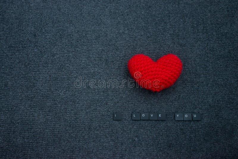Haga a ganchillo el corazón rojo en fondo y la inscripción negros te amo fotos de archivo