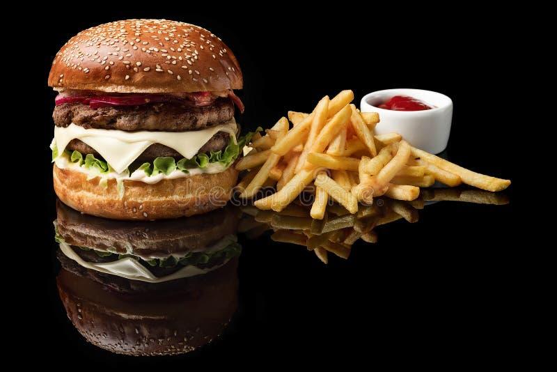 Haga la hamburguesa y las patatas fritas a mano, salsa de la carne de vaca aislada en fondo negro fotos de archivo libres de regalías