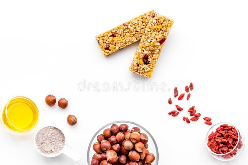 Haga las barras de granola calurosas con la harina de avena, las nueces, la miel y las bayas Espacio blanco de la copia de la opi fotos de archivo