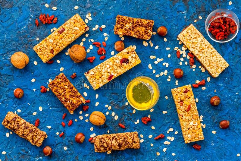 Haga las barras de granola calurosas con la harina de avena, las nueces, la miel y las bayas Opinión superior del fondo azul imagen de archivo libre de regalías