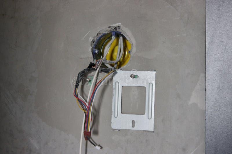 Haga las placas de pared para los interruptores y los receptáculos en el muro de cemento reparación en el apartamento o la casa c foto de archivo