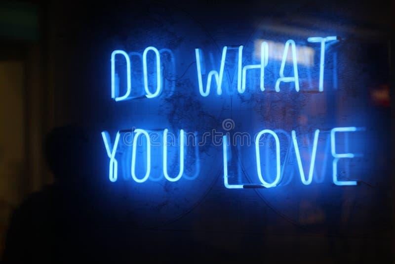 Haga lo que usted ama las luces de neón fotografía de archivo
