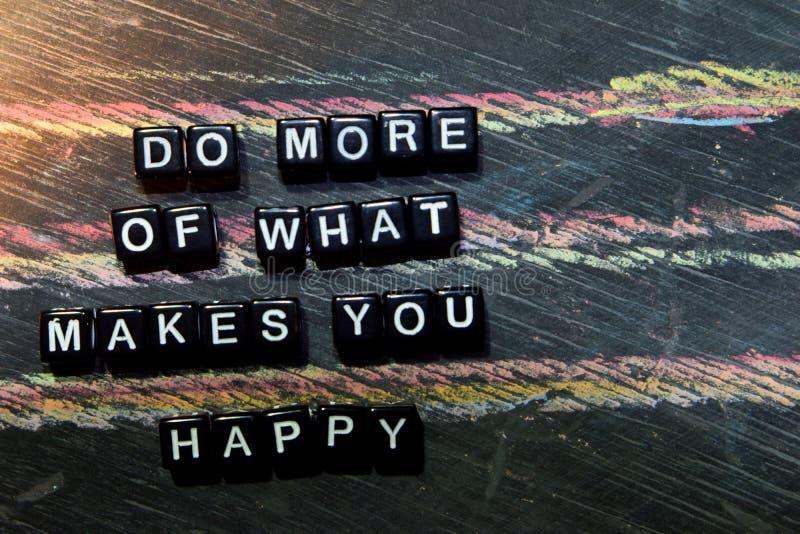 Haga más de qué le hace feliz en bloques de madera Imagen procesada cruzada con el fondo de la pizarra foto de archivo