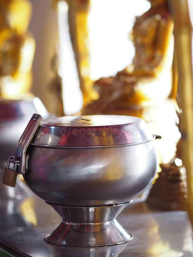 Haga para merecer el dinero de la oferta a los monjes puestos en cuenco de las limosnas foto de archivo