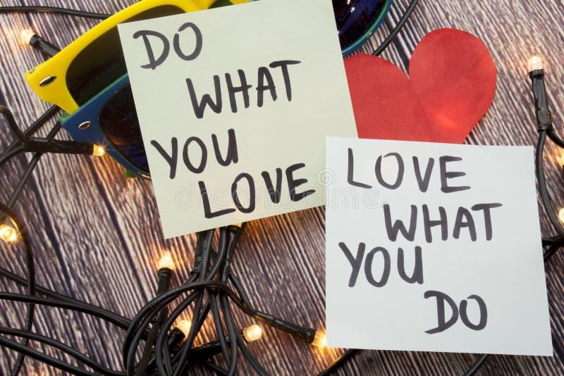 Haga qué usted aman, el amor qué usted lo hace - extracto de motivación de la palabra en el fondo de madera de la nota pegajosa foto de archivo libre de regalías