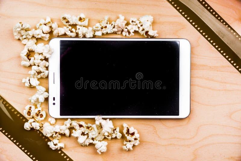 Haga tabletas la PC en la madera con cualidades del cine foto de archivo