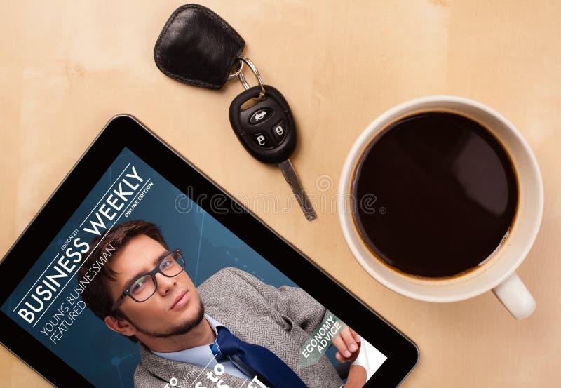 Haga tabletas la PC que muestra la revista en la pantalla con una taza de café en una d fotografía de archivo