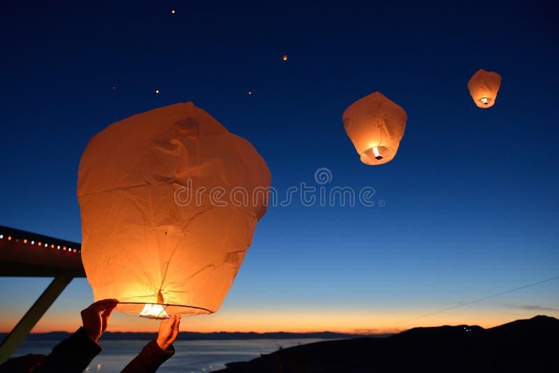 Haga un deseo, lanzamiento flotante de las linternas del papel en la montaña del urogallo imagenes de archivo