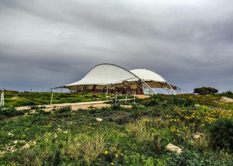 Hagar Qim and Mnajdra prehistoric temple complex with canopy, megalith temple under protective tent on the Mediterranean island of. Malta with blue sea in a royalty free stock photos