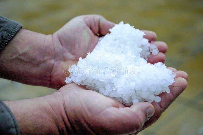 Hagel in een hand na onweer, klimaatveranderingconcept stock fotografie