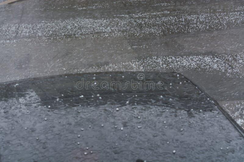 Hageldalingen op een zwart autodak stock afbeelding