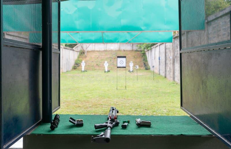Hagelgevär och handeldvapen med kulor på en grön tabell i skjutbana Skytte för utbildning för pistol för övningsbrand royaltyfri foto
