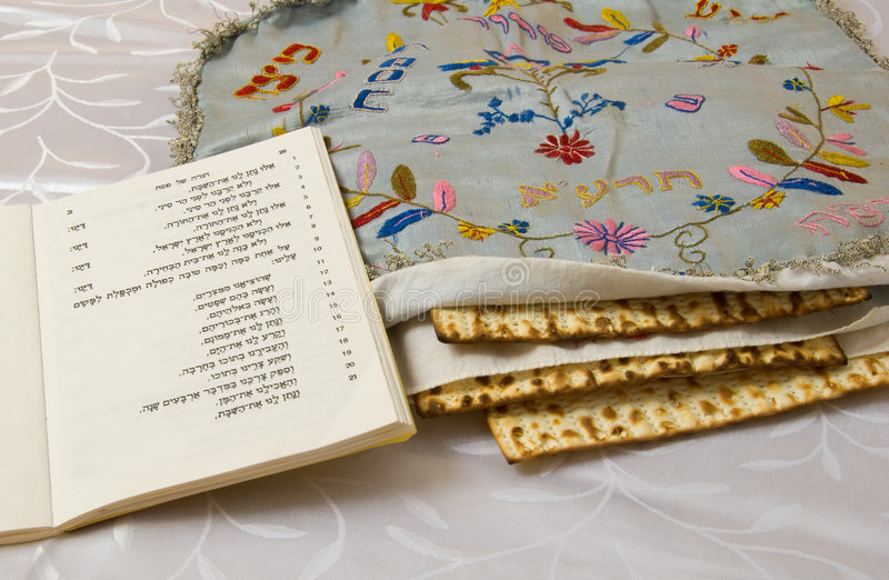 Haggadah and Matzo. Passover Haggadah (tradtional account of the Exodus from Egypt) with hand-enbroidered matzah cover and stack of 3 matzohs stock images