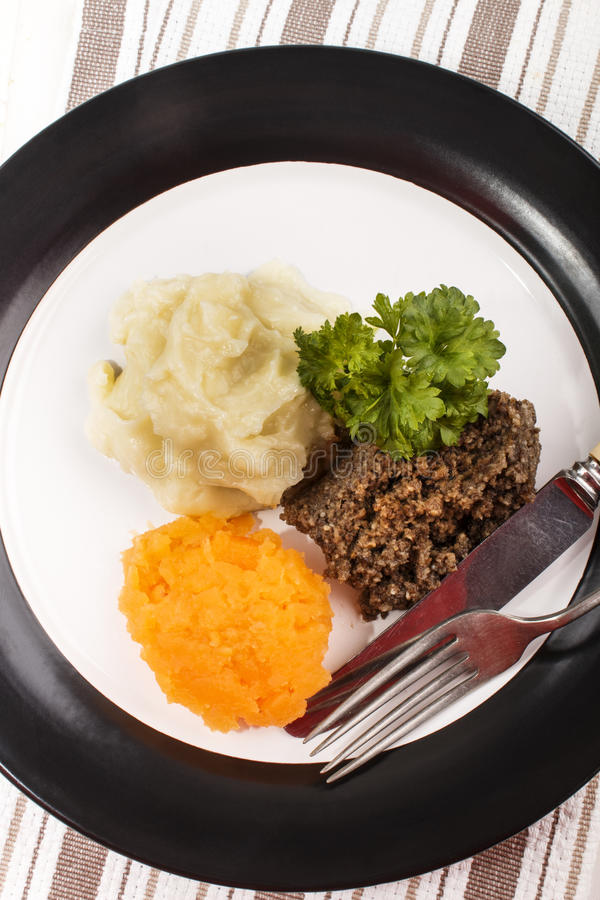 Haggis met fijngestampte aardappel, raap en peterselie op een plaat royalty-vrije stock foto