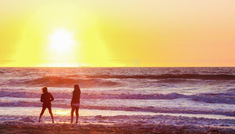 Girls people on beach surf sunset enjoying walk trowing rocks water sea ocean waves royalty free stock photos