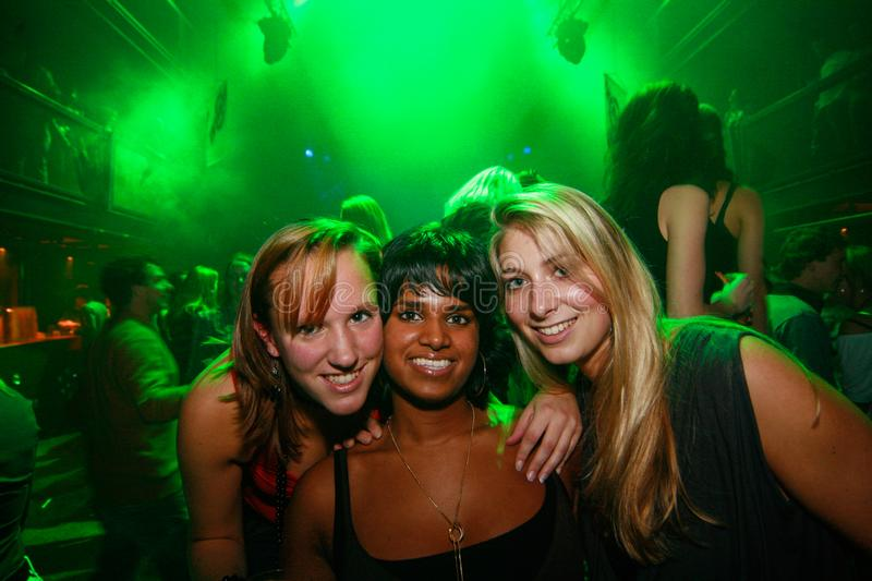 Clubs and nightlife bar at night party dance floor tree people posing for picture green light stock photo