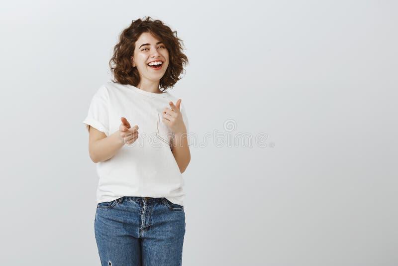 Haha, ama sus bromas Freelancer joven y creativo alegre con el pelo rizado, riendo hacia fuera ruidosamente de emociones positiva imagen de archivo