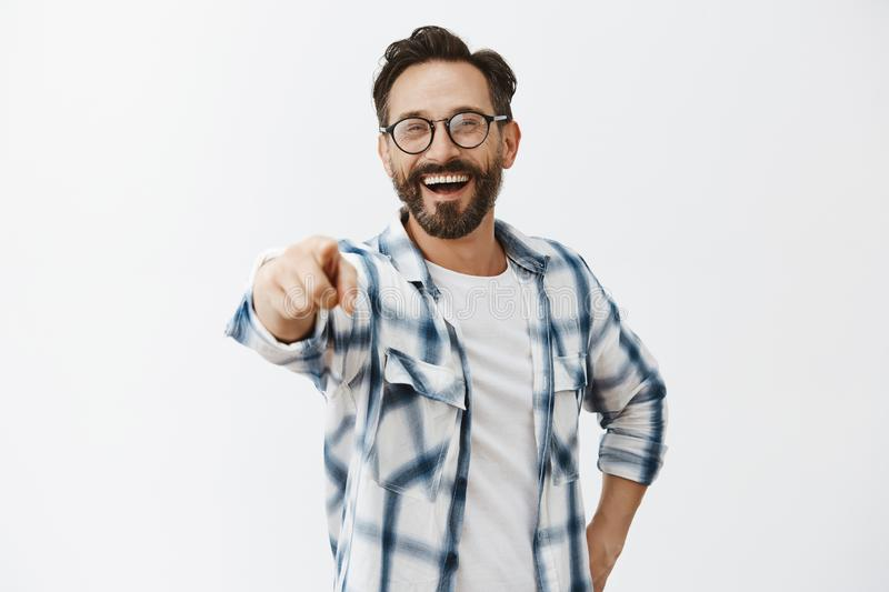 Haha got you. Portrait of carefree funny and emotive handsome mature coworker with beard in checked shirt and glasses royalty free stock photos