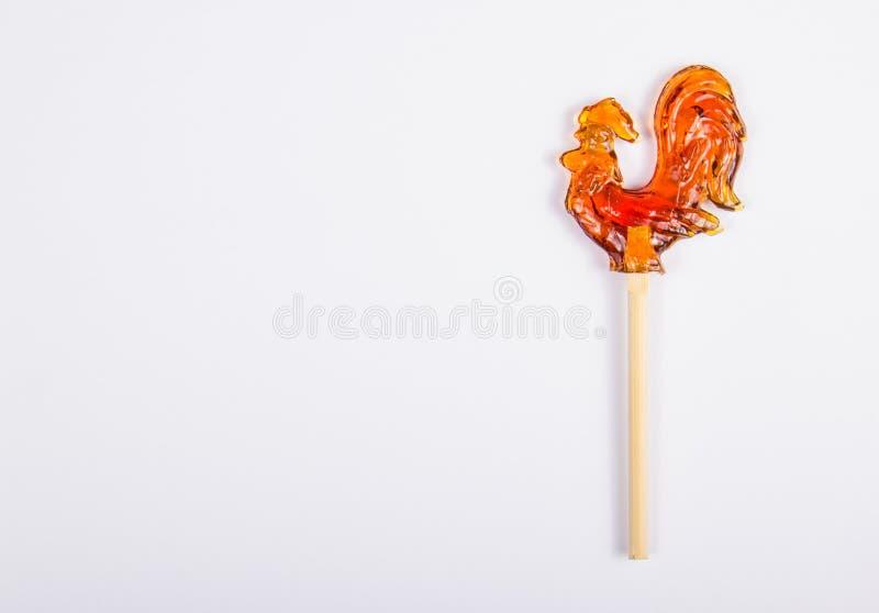 Hahn auf einem Stock auf einem weißen Hintergrund Russische Süßigkeiten Lutscher in Form eines Hahns lizenzfreie stockfotos