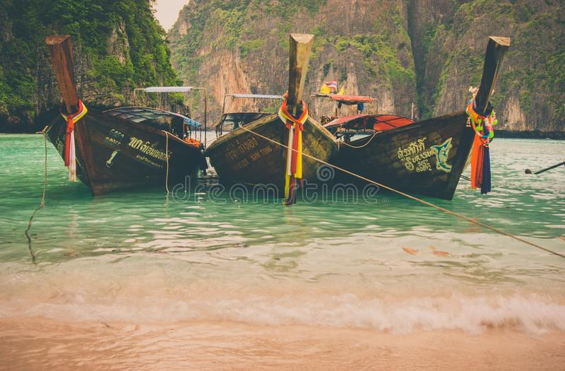 Hai traditional wooden boat with ribbon decoration at ocean shore under blue sky.Thailand tropical beach landscape, Krabi province stock photography