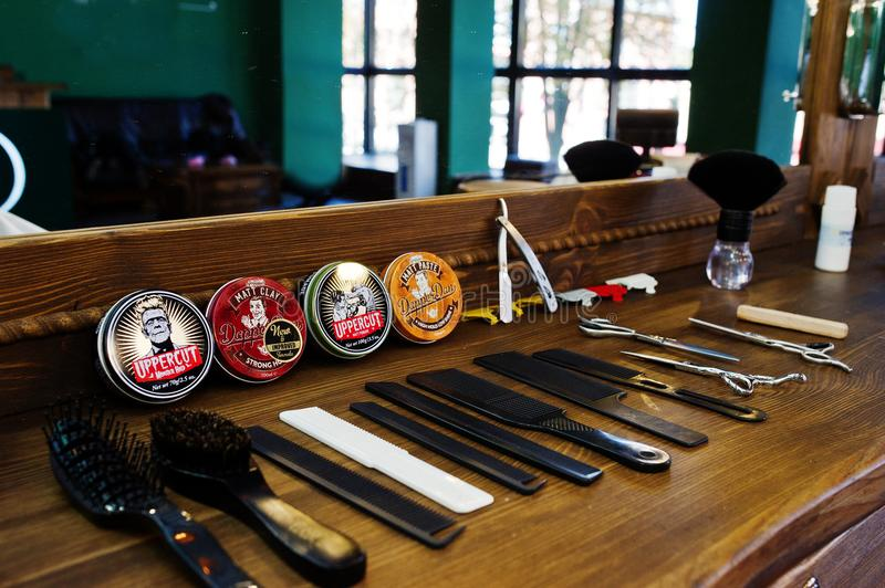Hai, Ukraine - 08 November, 2017: Dapper Dan and Upperut hair w. Axes or clays or pomades, combs and scissors on the wooden surface in barbershop stock image