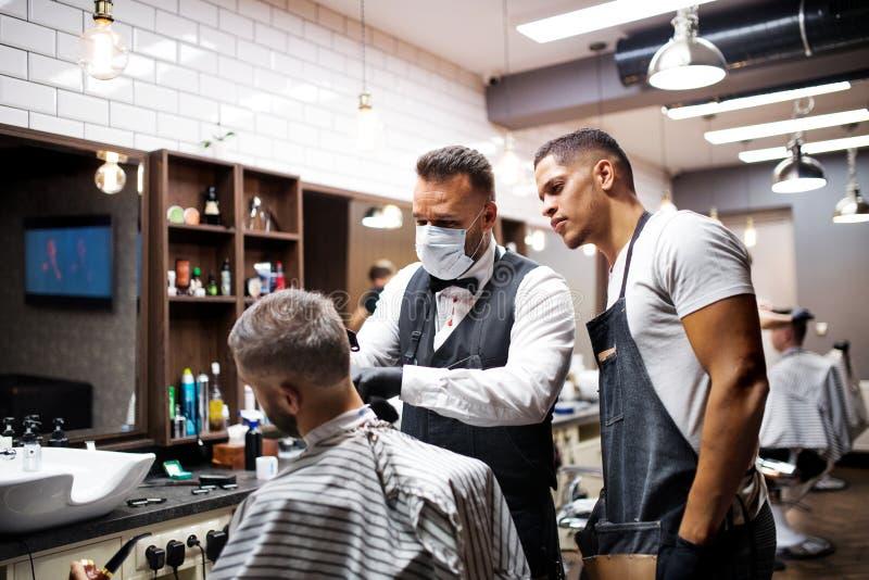 Haidresser e barbeiro de visita do cliente do homem do moderno na barbearia, conceito de formação fotos de stock royalty free