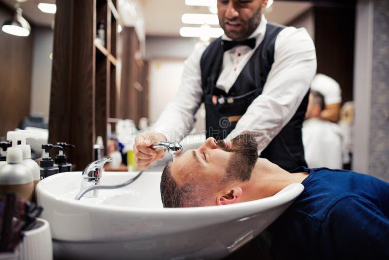 Haidresser e parrucchiere di visita del cliente dell'uomo dei pantaloni a vita bassa nel negozio di barbiere immagine stock libera da diritti