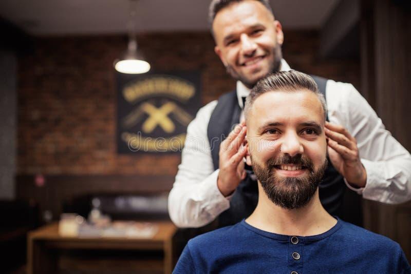 Haidresser y peluquero que visitan del cliente del hombre del inconformista en peluquería de caballeros Copie el espacio imagen de archivo libre de regalías