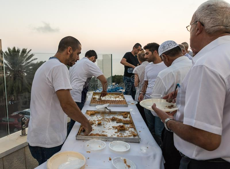 Believers treat visitors with sweets in the evening in the courtyard of the Ahmadiyya Shaykh Mahmud mosque in Haifa city in Israel. Haifa, Israel, July 11, 2019 royalty free stock photos