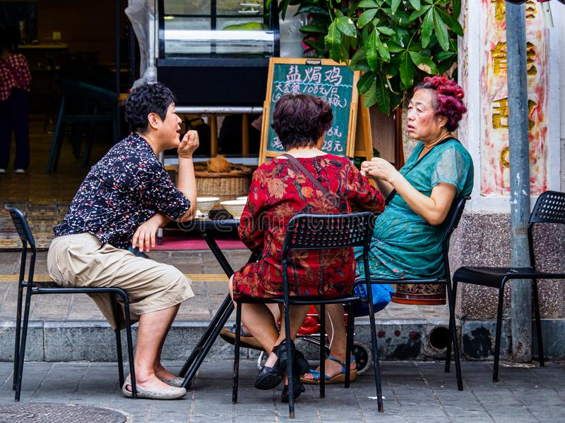 HAIKOU, HAINAN, CHINA - MAR 2 2019 - Middle-aged Asian Chinese women chat outside a cafe. China has a rapidly aging population stock photography