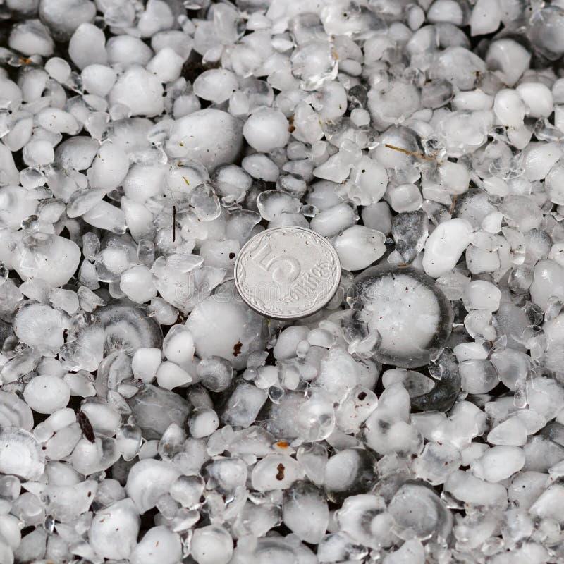 Оклик с определенными размерами с более большой монеткой, градины на том основании после hailstorm, оклика большего размера стоковые изображения rf