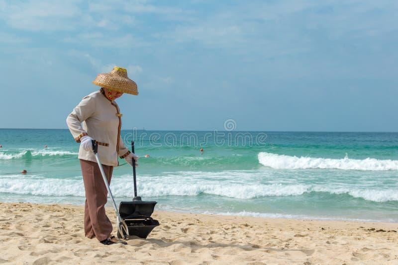 Hainan ö, Sanya, Kina - Maj 16, 2019: En städerska väljer upp avfall på den Hainan stranden med special behändig kirurgisk tång royaltyfri fotografi