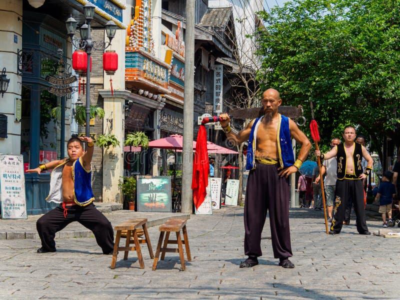 HAINAN, CHINA - 3 MAR 2019 – Asian Chinese martial artists perform in traditional costume at Feng Xiaogang movie town, Hainan. HAINAN, CHINA - 3 MAR 2019 royalty free stock image