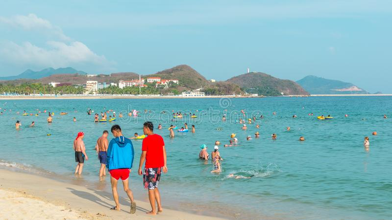 Hainan, China - May 14, 2019: On a bright sunny day on a tropical beach, people swim in the sea, relax on the sand.  stock photography