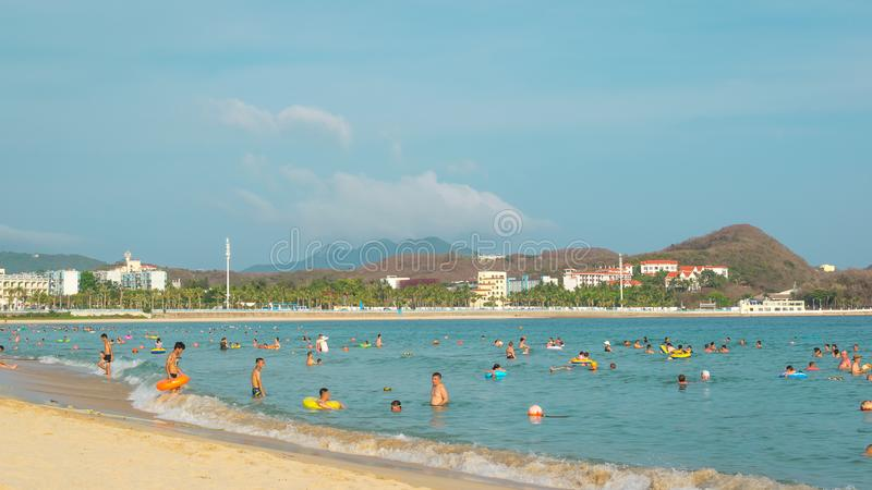 Hainan, China - May 14, 2019: On a bright sunny day on a tropical beach, people swim in the sea, relax on the sand.  royalty free stock photos